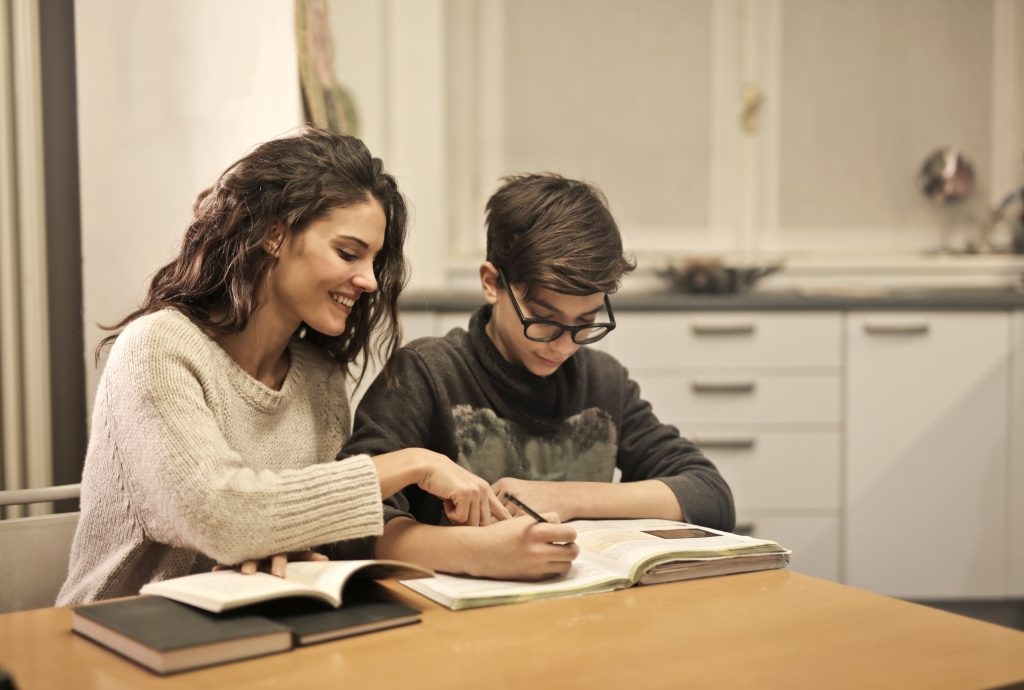 Canva - Elder sister and brother studying at home
