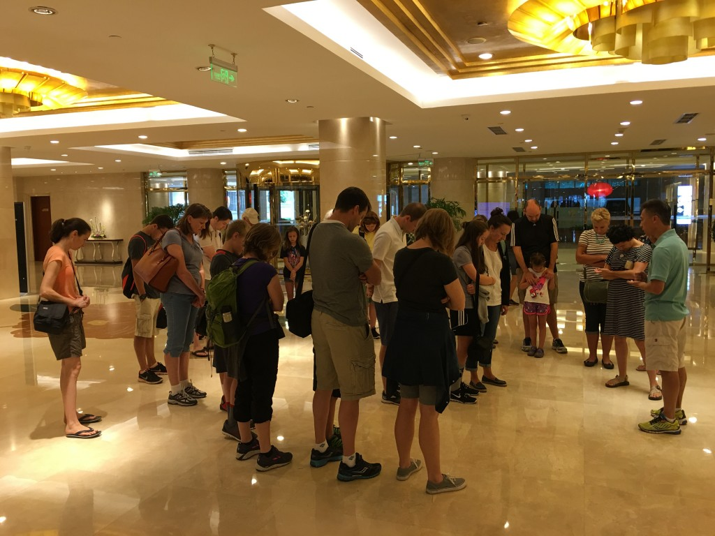 CCAI Co-Founder Joshua Zhong leads families in prayer at a hotel in Beijing
